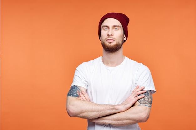 Homem com uma camiseta branca e uma tatuagem de chapéu nos braços com fundo laranja