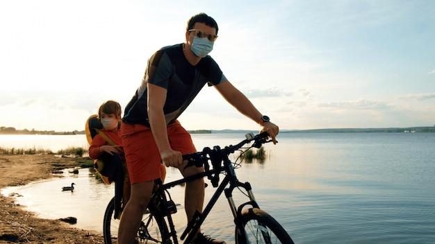 Homem com uma criança em uma bicicleta em máscaras protetoras