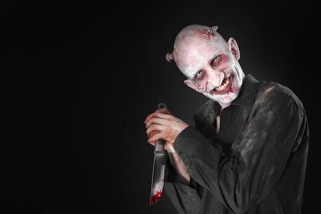 Homem com uma faca ensanguentada disfarçada de zumbi em um fundo preto.