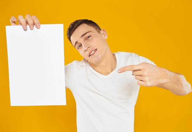Homem com uma folha de papel branca em um gerente de marketing de publicidade amarelo