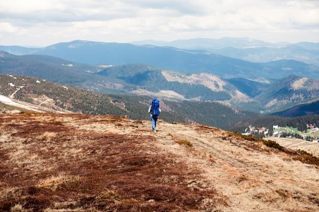 Homem com uma grande mochila na montanha, viajante de montanha com uma mochila grande