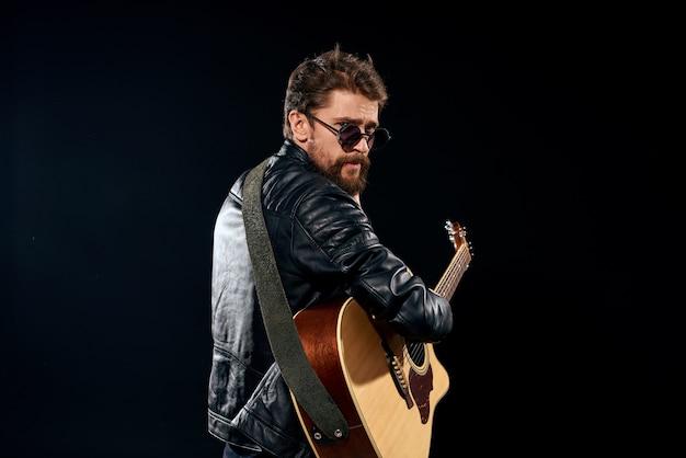 Homem com uma guitarra nas mãos, jaqueta de couro preta, óculos de sol, música, emoções