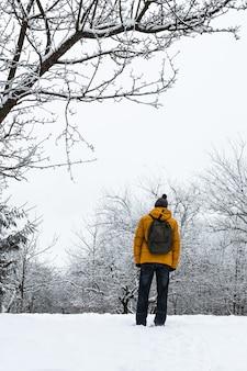 Homem com uma jaqueta laranja e uma mochila verde em uma paisagem de inverno