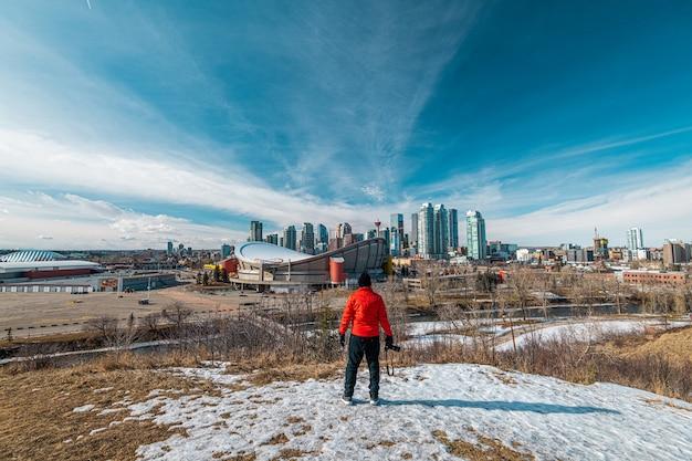 Homem com uma jaqueta vermelha olhando para a cidade de calgary em alberta, canadá