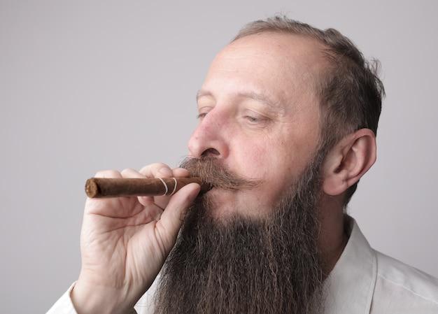Homem com uma longa barba e bigode fumando um charuto com uma parede cinza