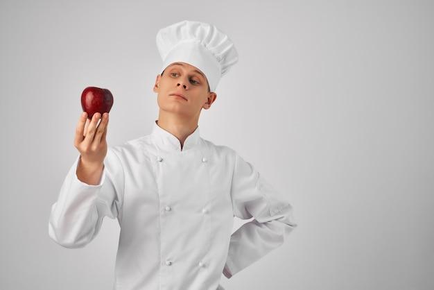 Homem com uma maçã nas mãos. uniforme de chef trabalha em restaurante profissional