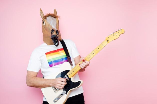 Homem com uma máscara de cavalo, tocando guitarra elétrica.