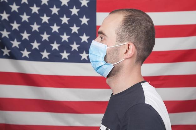 Homem com uma máscara médica no fundo da bandeira americana.