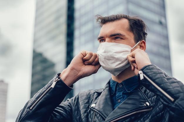 Homem com uma máscara protetora de pé em uma rua da cidade. foto com cópia-espaço
