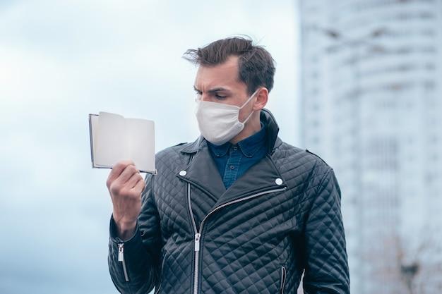 Homem com uma máscara protetora, olhando para a entrada em seu passaporte. conceito de segurança