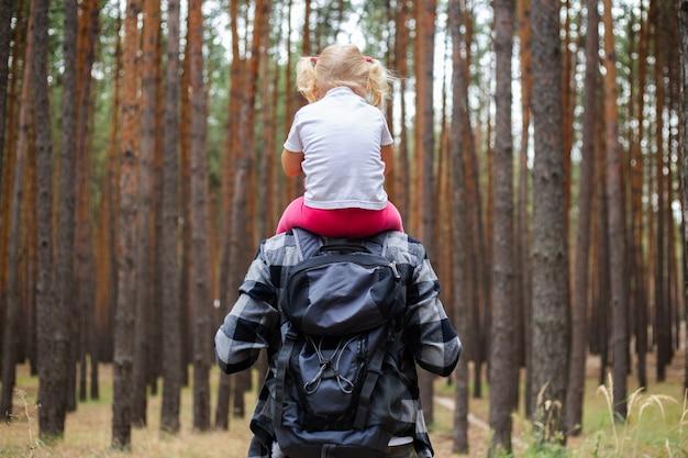 Homem com uma mochila carrega uma criança nos ombros na floresta. caminhada em família para as montanhas ou floresta.