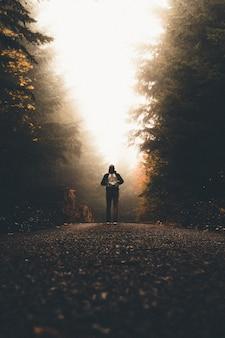Homem com uma mochila parado em um caminho entre árvores altas e grossas, olhando para a luz