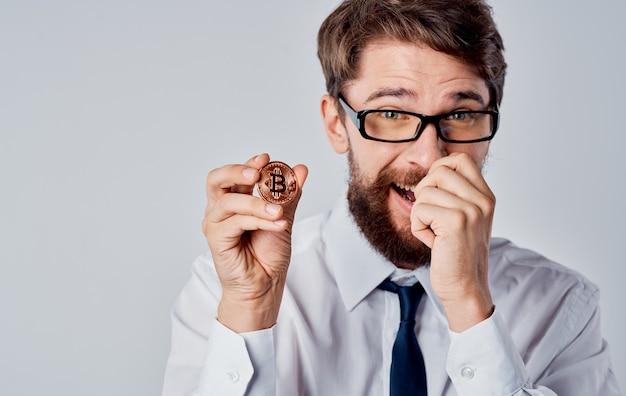 Homem com uma moeda na mão sucesso alegria criptomoeda bitcoin fundo cinza copiar espaço. foto de alta qualidade