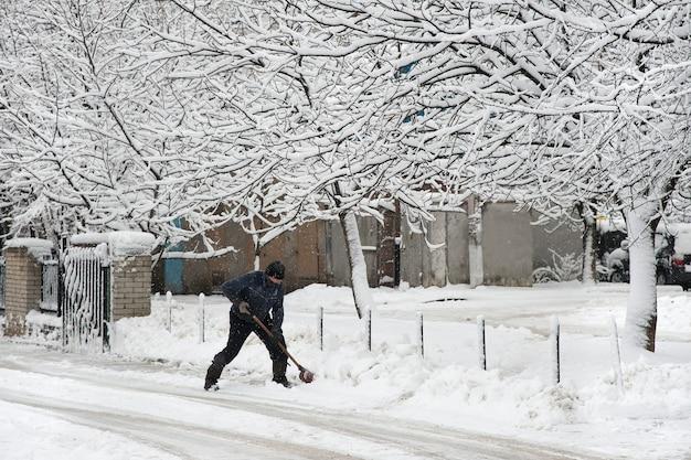 Homem com uma pá de neve, limpando a neve da garagem.