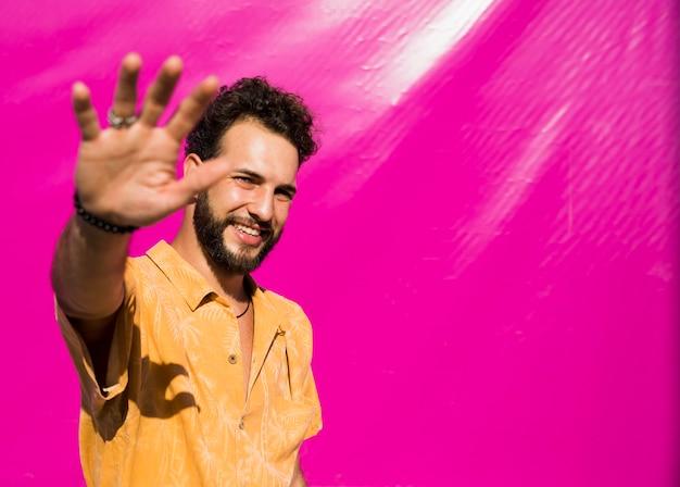 Homem com uma parede rosa atrás de olhar para a câmera