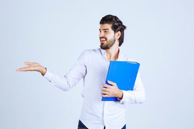Homem com uma pasta azul apresentando seu colega à esquerda