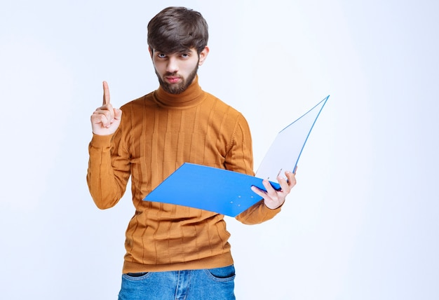 Homem com uma pasta azul, levantando o dedo para chamar a atenção. h
