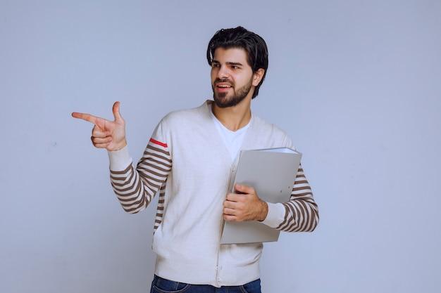 Homem com uma pasta de relatórios e apontando alguém à esquerda.