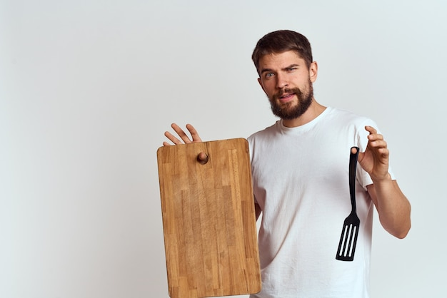 Homem com uma placa de madeira da cozinha e uma pá acesa