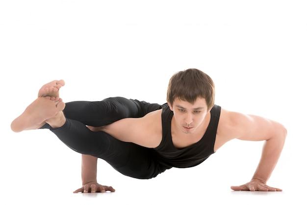 Homem com uma postura de yoga difícil