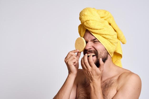 Homem com uma toalha amarela na cabeça, ombros nus, esponja, pele limpa, cuidado facial