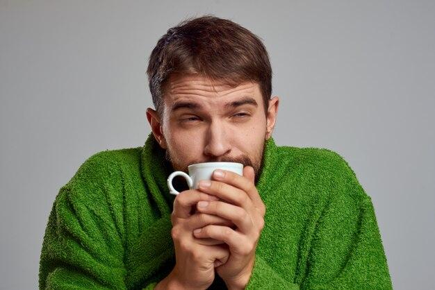 Homem com uma túnica verde com um copo de bebida nas mãos em uma visão recortada de cinza.