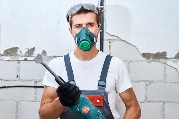 Homem com uniforme de construtor com furadeira faz reparos na sala. conceito de renovação