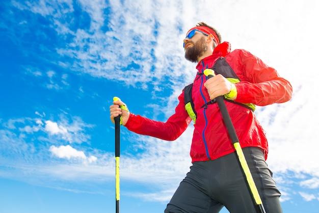 Homem com varas entre caminhada nórdica com fundo do céu