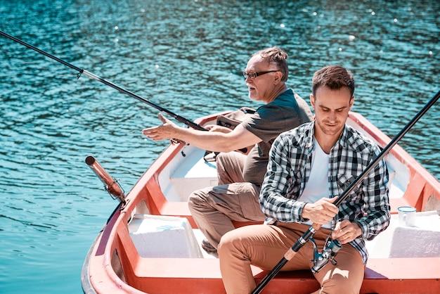 Homem com velhinho pescando em um barco a remo