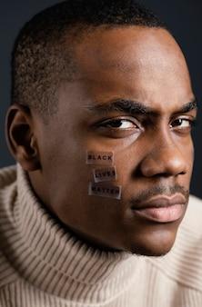 Homem com vida negra importa mensagem no rosto
