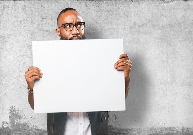 Homem com vidros atrás de um cartaz em branco
