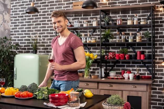 Homem com vinho. homem bonito e barbudo loiro com músculos em pé na cozinha e bebendo vinho