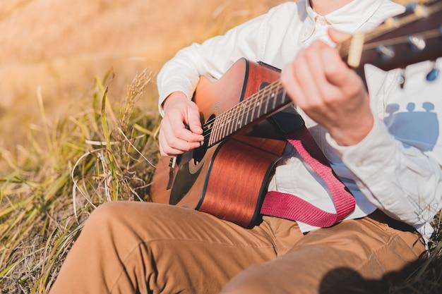 Homem com violão no campo. cantor-compositor tocando uma música ao ar livre, o conceito de inspiração musical na natureza