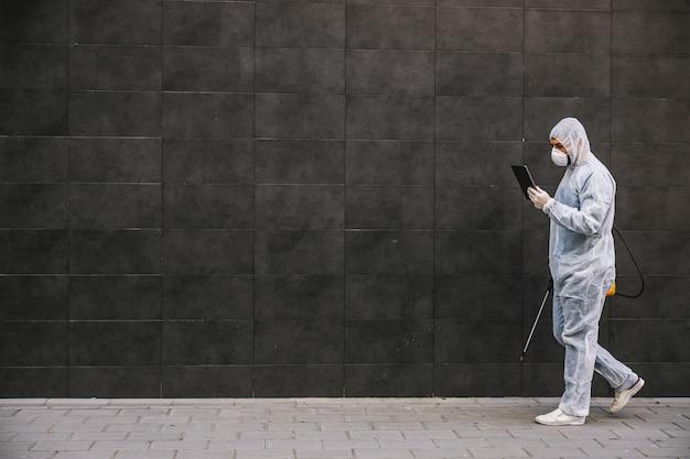 Homem com vírus e terno e máscara olhando e digitando no tablet, desinfetando edifícios de covid-19 com o pulverizador. prevenção de infecções e controle de epidemia. pandemia mundial.
