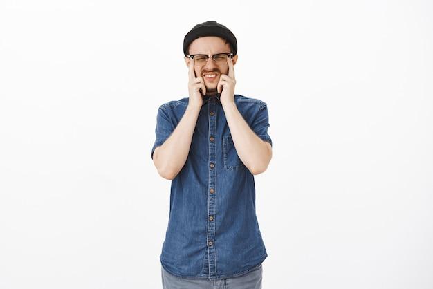 Homem com visão ruim tocando os olhos e semicerrando os olhos de óculos fazendo careta durante o exame oftalmológico em loja de ótica em pé intenso e concentrado, precisando usar óculos prescritos