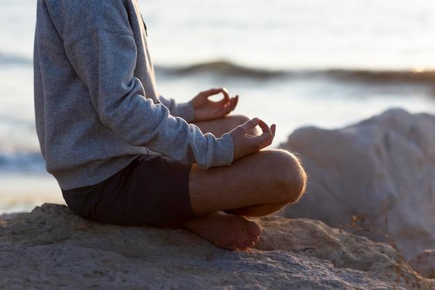 Homem com vista lateral relaxando na praia