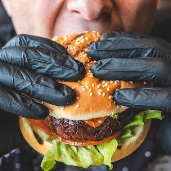 Homem come hambúrguer de carne suculenta. fechar-se
