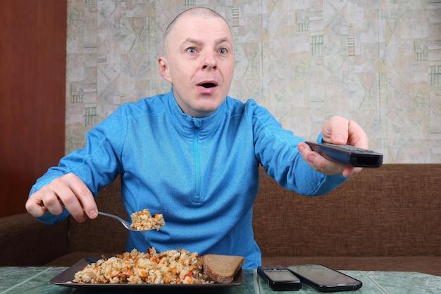 Homem come plov e emocionado assistindo tv