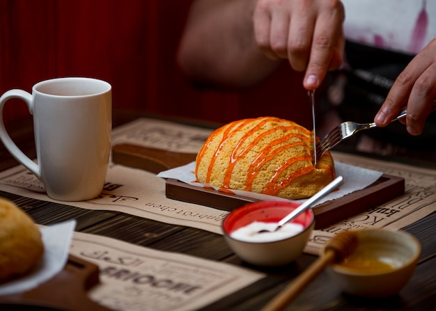 Homem come um pão branco coberto com caramelo