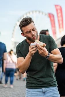 Homem comendo comida de rua. hotdogs de rua