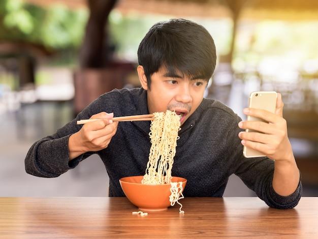 Homem comendo enquanto olhando e usando smartphone