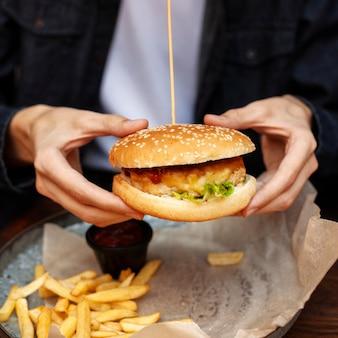 Homem comendo hambúrguer com batatas fritas