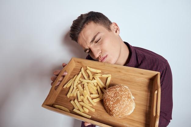 Homem comendo palete de madeira fast-food batata frita hambúrguer diet comida restaurante