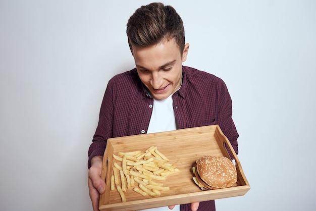 Homem comendo palete de madeira fast-food batatas fritas hambúrguer dieta comida restaurante luz de fundo. foto de alta qualidade