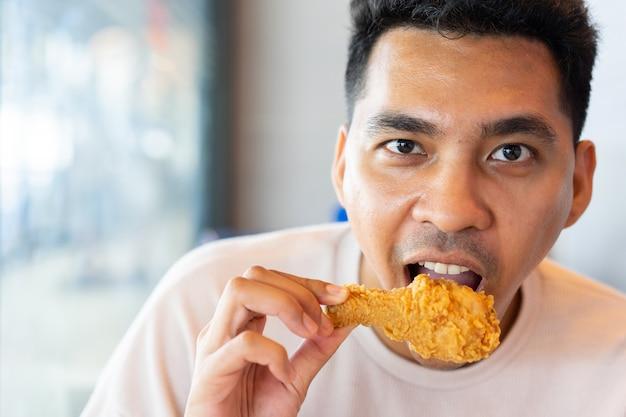 Homem comendo perna de frango frito na refeição de brunch no restaurante com felicidade em tempo de relaxar