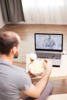 Homem comendo pipoca durante uma chamada de vídeo com seu amigo durante o isolamento.