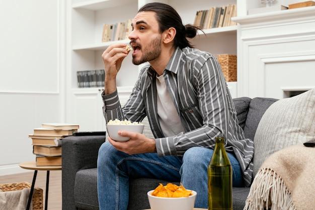 Homem comendo pipoca e assistindo tv no sofá