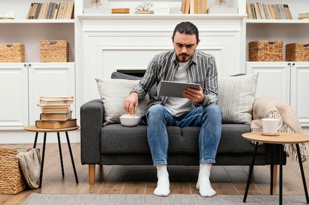 Homem comendo pipoca e segurando um tablet digital