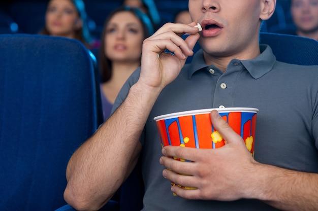 Homem comendo pipoca no cinema. imagem recortada de um jovem comendo pipoca e assistindo um filme enquanto está sentado no cinema