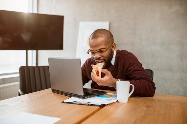 Homem comendo pizza durante o intervalo da reunião do escritório